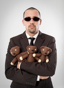 Ritratto esecutivo che abbraccia un orsacchiotto su sfondo neutro
