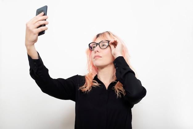 Donna esecutiva che adegua i suoi occhiali con il suo specchio del telefono cellulare su sfondo bianco