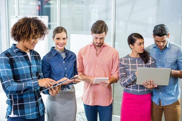 Dirigenti che utilizzano laptop, tablet digitale e telefono cellulare