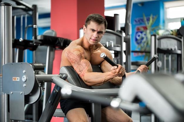 Esercizio per bicipiti. giovane culturista che fa esercizio pesante per il bicipite