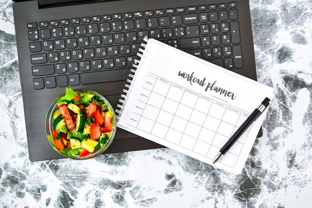 Piano di esercizi per una settimana e ciotola con insalata di verdure sul posto di lavoro vicino al computer
