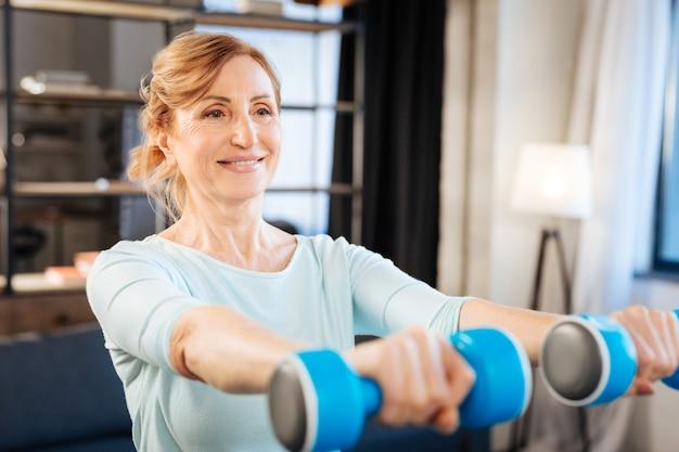 Esercizi con manubri. signora adulta positiva che solleva manubri pesanti mentre si allena a casa con attrezzature speciali