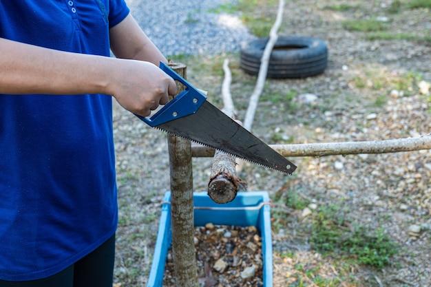 La mano esercitata utilizza una sega a mano per tagliare tronchi da utilizzare in vari compiti.