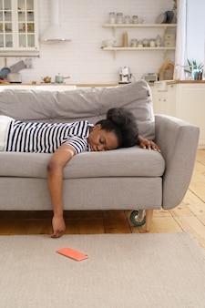 Esaurita donna afro-americana che dorme sul divano a casa, lasciando cadere il cellulare sul pavimento. fatica