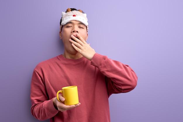 Studente asiatico esausto con la tazza in mano che sbadiglia, vuole dormire prima della scuola o dell'università