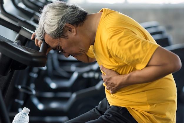 Esausto blackout vecchio dopo l'esercizio in bicicletta sulla macchina in palestra. ragazzo anziano a testa in giù a causa di un attacco di cuore. anziano incidente da allenamento sportivo. sanità e assicurazione per pensionato anziano.