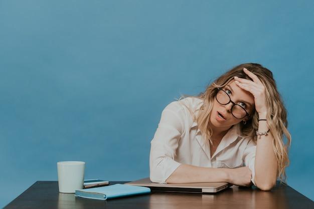 Esausto bionda con gli occhiali che indossa camicia bianca seduto al suo posto di lavoro con il computer portatile, sembra stanco, annoiato a casa durante la quarantena su sfondo blu. concetto di pandemia di coronavirus.