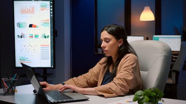 Donna d'affari esausta che analizza le statistiche di marketing sul computer portatile che lavora nell'ufficio della società di avvio stanco manager maniaco del lavoro rimane solo nella stanza finanziaria dopo che il suo collega se ne è andato