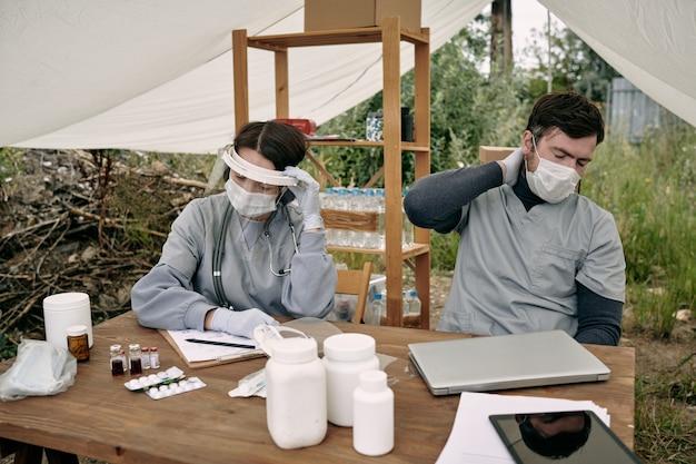 Operatori sanitari esausti in maschera seduti a tavola con pillole sotto il tetto della tenda mentre lavorano con ...