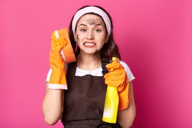 Detergente emotivo esaurito che sta isolato sopra il rosa in studio, tenendo la pezzuola per lavare vicino all'orecchio e detergente