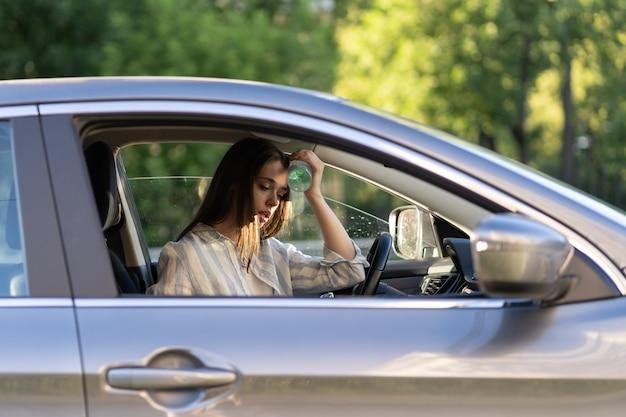 L'autista esausto della ragazza che soffre di mal di testa fa caldo applica una bottiglia d'acqua sulla fronte