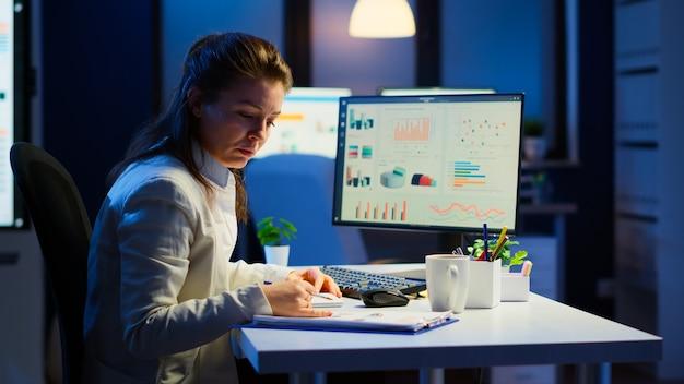 Manager esausto che cerca di finire il progetto aziendale rispettando la scadenza lavorando di notte davanti al computer che prende appunti scrivendo sul taccuino. straordinario stanco del dipendente seduto alla scrivania sul posto di lavoro