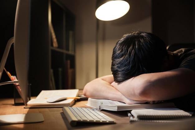 Giovane esausto oberato di lavoro che studia e dorme sul tavolo in una stanza buia a casa