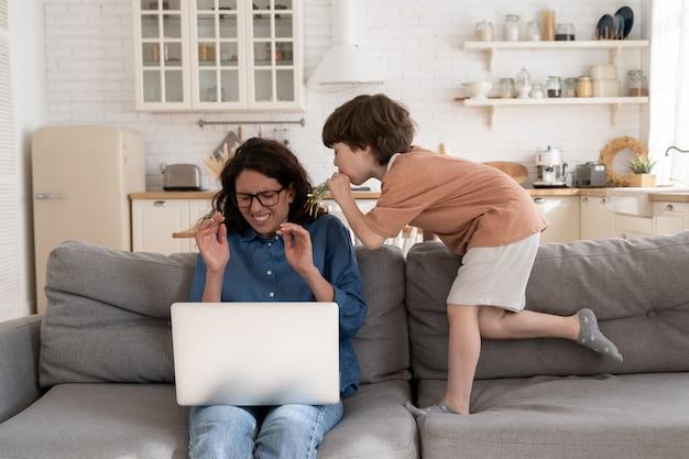 Una madre single esausta lavora da casa in isolamento con un figlio in età prescolare testardo dal laptop