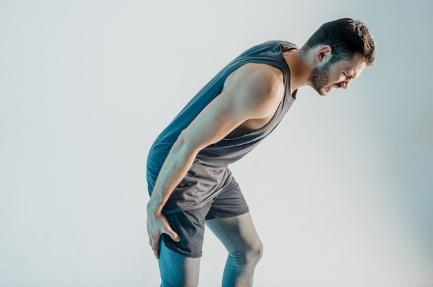 Sportivo esausto che sente dolore alle gambe. il giovane uomo europeo barbuto indossa l'uniforme sportiva. concetto di infortunio sportivo. isolato su sfondo turchese. riprese in studio. copia spazio