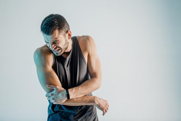 Sportivo esausto che sente dolore al gomito. il giovane uomo europeo barbuto indossa l'uniforme sportiva. concetto di infortunio sportivo. isolato su sfondo turchese. riprese in studio. copia spazio