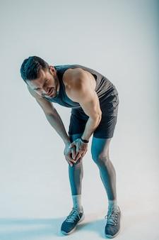 Sportivo esausto che sente dolore al ginocchio. il giovane uomo europeo barbuto indossa l'uniforme sportiva. concetto di infortunio sportivo. isolato su sfondo turchese. riprese in studio