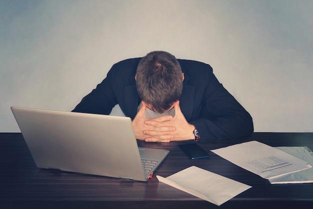 Uomo d'affari stanco esausto che lavora al computer portatile in ufficio, massaggia l'area temporale, tiene gli occhiali, sente disagio da fatica, affaticamento degli occhi dopo aver indossato a lungo gli occhiali, problemi alla vista,