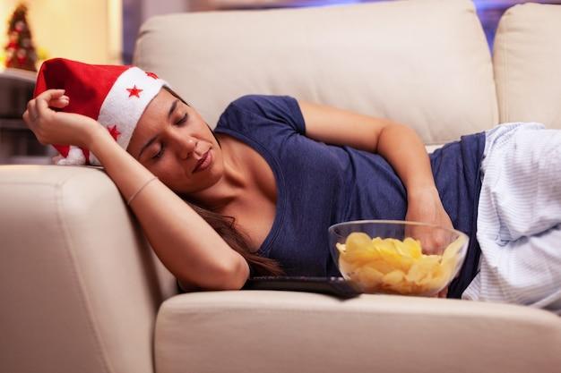 Donna esausta che si addormenta sul divano mentre guarda un film di natale