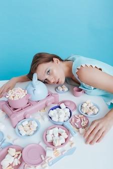 Esausta giovane donna sdraiata sul tavolo con piatti di plastica e marshmallow