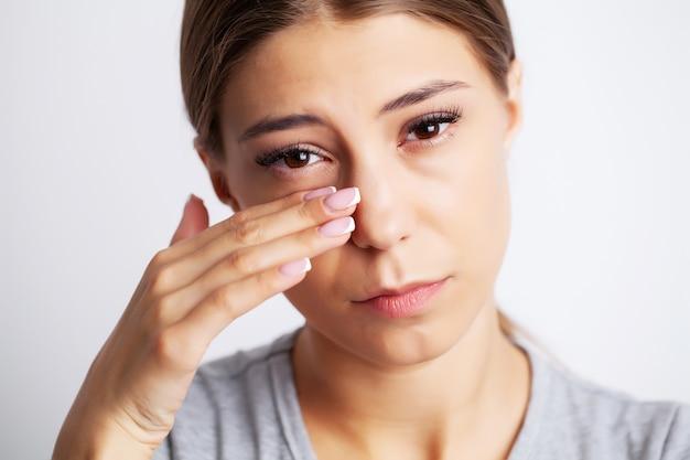 Esausta giovane donna che soffre di forti dolori da vicino agli occhi