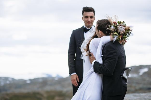 Esci dalla cerimonia in cima alla montagna, lo sposo abbraccia la sposa sullo sfondo del maestro delle cerimonie