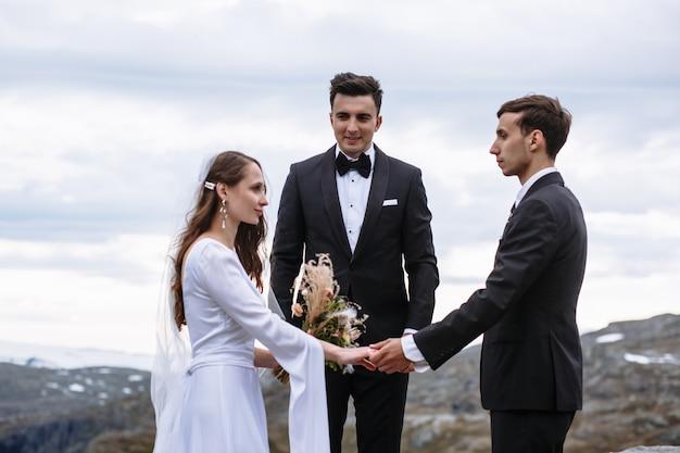 Esci dalla cerimonia in cima alla montagna, lo sposo tiene la mano della sposa sullo sfondo del maestro delle cerimonie