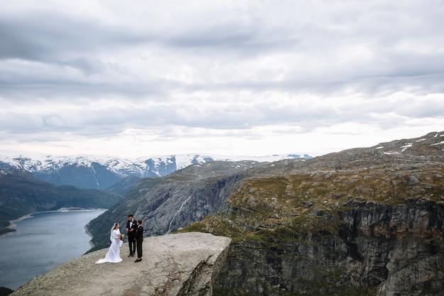 Esci dalla cerimonia di nozze su un frammento di roccia in norvegia chiamato la lingua di troll