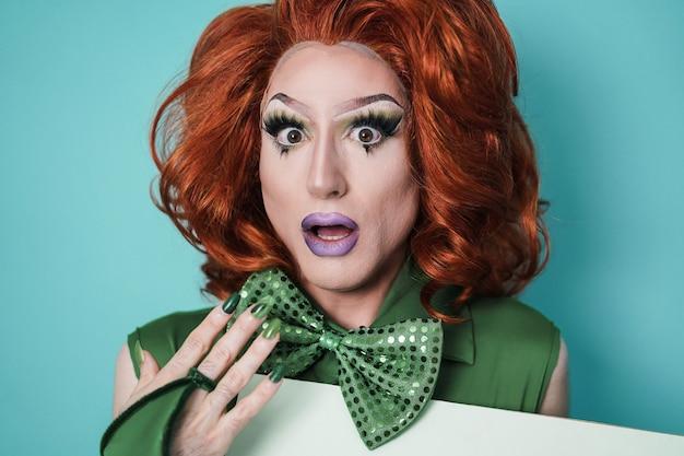 Drag queen uscito che guarda la telecamera con sfondo turchese - concetto lgbtq - focus on face
