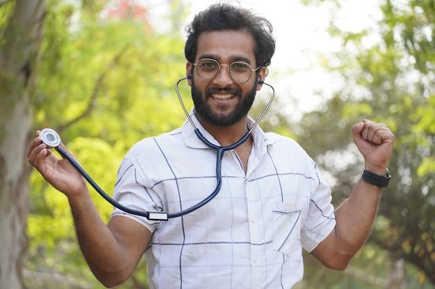 Uno studente uscito che mostra lo studente del collage dello stetoscopio con lo stetoscopio e che mostra il concetto di formazione medica del segno di successo