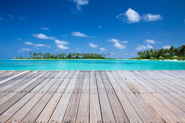 Sfondo spiaggia esotica con supporto in legno e mare tropicale