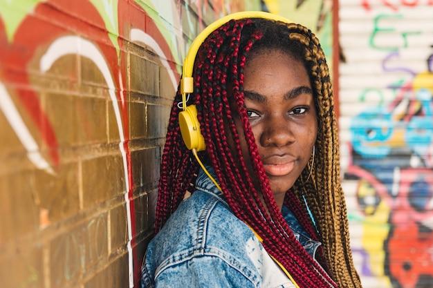 Esotica ragazza nera con trecce colorate tra i capelli e le cuffie gialle che ascolta la musica. appoggiato a un muro di graffiti.