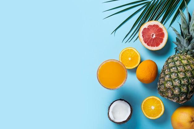 Frutti esotici su sfondo blu. ananas, cocco, arancia, pompelmo