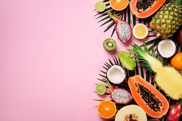 Frutta esotica e foglie di palma tropicale - papaya, mango, ananas, banana, carambola, frutta del drago, kiwi, limone, arancia, melone, cocco, lime.