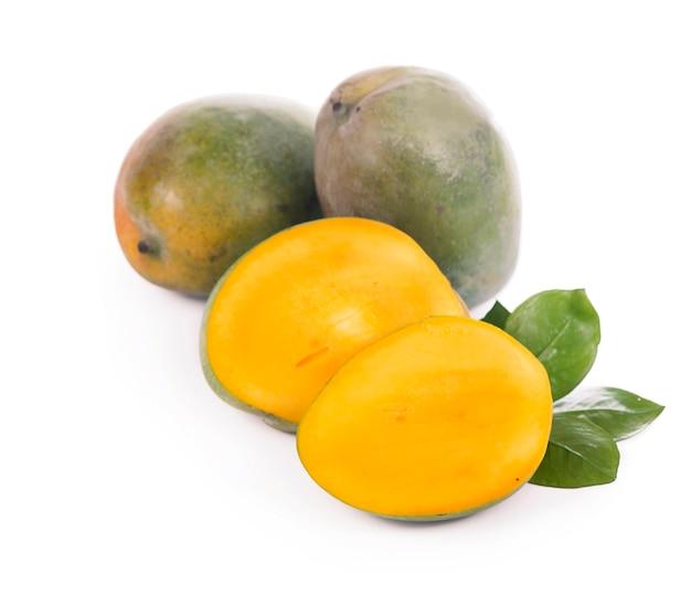 Frutti e foglie succosi esotici del mango isolati sulla superficie bianca