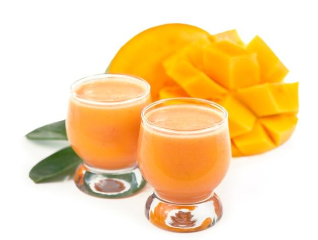 Frutti di mango succosi esotici e due bicchieri di succo di mango naturale fresco isolato su priorità bassa bianca