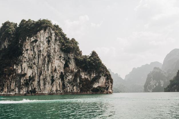 Isole esotiche e tropicali verde scuro con rocce e lago verde a cheow lan lake, khao phang, distretto di ban ta khun