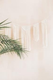 Rami di palma tropicali esotiche e decorazioni in stile boho su sfondo beige pastello pallido