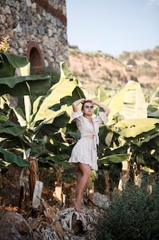 Donna tropicale esotica vicino alle foglie verdi del cespuglio di banana. ragazza dell'isola tropicale in vacanza