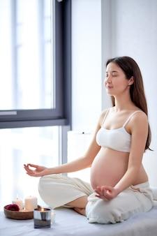 La giovane donna in attesa pratica lo yoga nella stanza luminosa, la salute durante la gravidanza. la futura mamma in abito casual, seduta con le gambe incrociate, meditando. maternità, gravidanza armoniosa. copia spazio