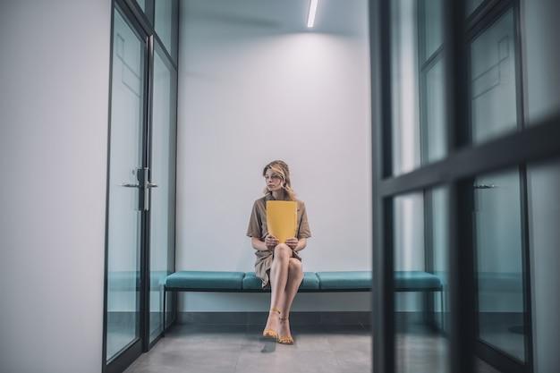 Aspettativa. giovane donna bionda pensierosa in abito con cartella gialla seduto nel corridoio dell'ufficio illuminato