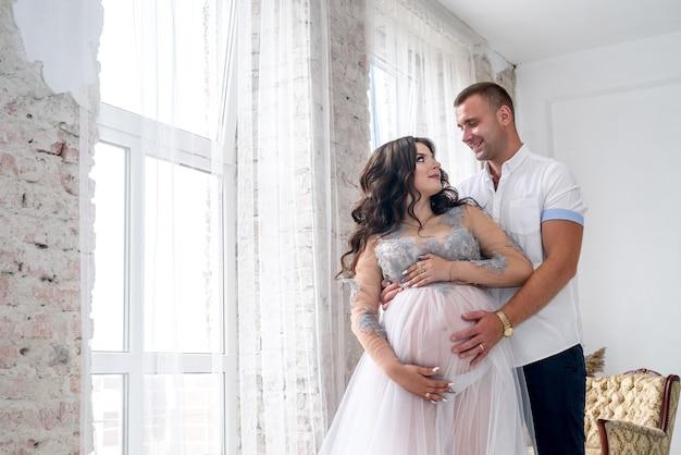 Nell'attesa. felice coppia incinta in abiti di moda in posa in studio