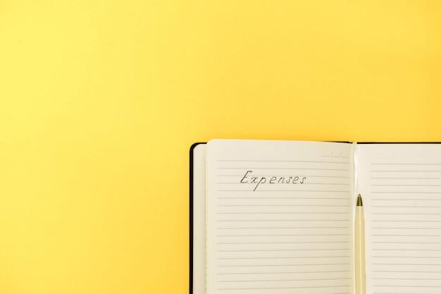 Spese e concetto di pianificazione del bilancio. vista dall'alto del blocco note con le parole scritte a mano spese