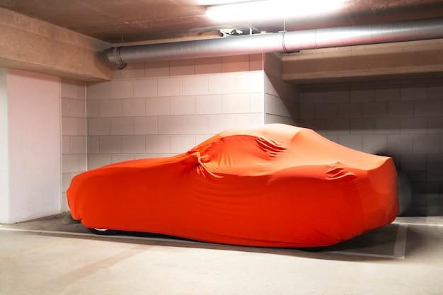 Nuova auto costosa con copertura arancione per protezione parcheggiata in garageauto sportiva moderna