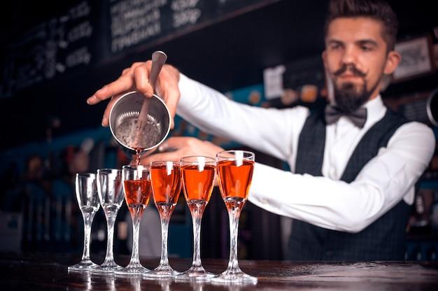 Barista esperto che versa bevande alcoliche fresche nei bicchieri della discoteca