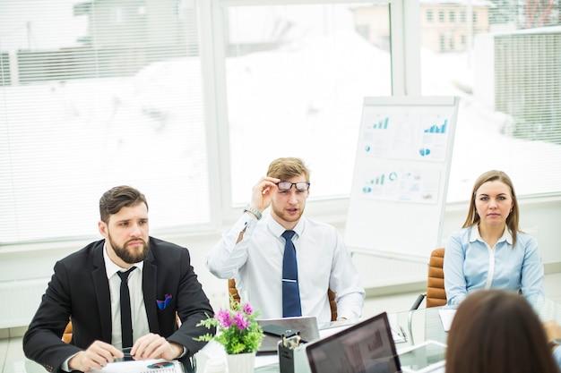 Il manager esperto di crisi e il team aziendale hanno condotto una riunione di lavoro in un ufficio moderno. la foto ha uno spazio vuoto per il testo