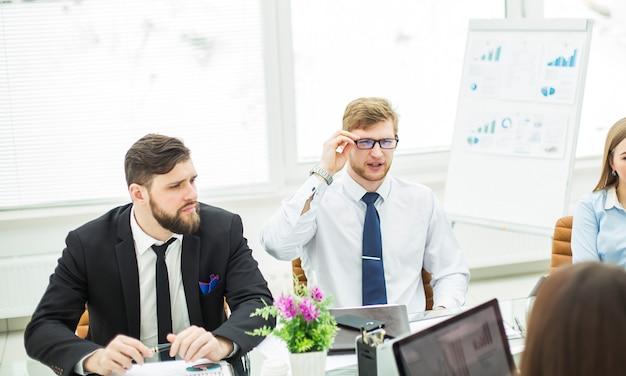 Il manager esperto di crisi e il team aziendale hanno condotto una riunione di lavoro in un ufficio moderno