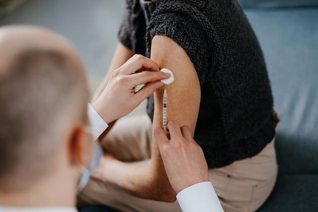 Medico esperto in maschera fa la vaccinazione nel suo ufficio