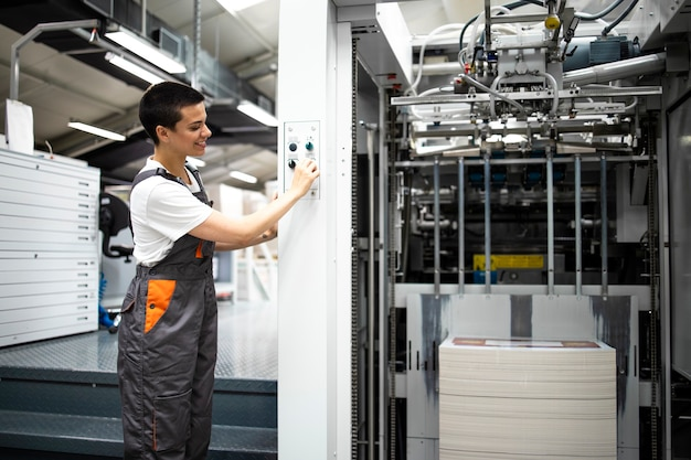 Una stampatrice esperta che avvia una moderna macchina da stampa nella tipografia.