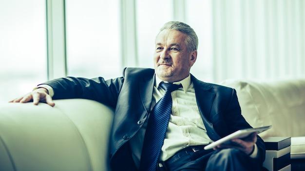 Avvocato esperto con tablet digitale seduto sul divano in t